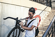 Young man carrying fixie bike downstairs - VPIF00182