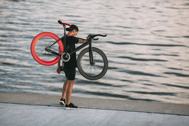 Young man carrying fixie bike at the waterfront - VPIF00197