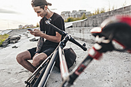 Young man sitting next to fixie bike using cell phone - VPIF00200