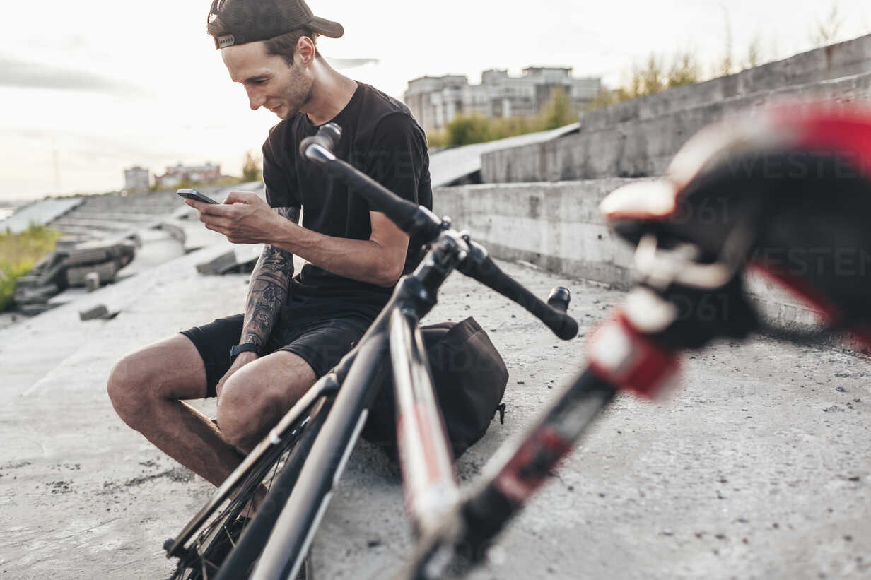 Young man sitting next to fixie bike using cell phone - VPIF00200 - Vasily Pindyurin/Westend61
