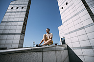 Young man with longboard surrounded by modern architecture - VPIF00206