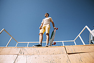 Young man with longboard on top of halfpipe in skatepark - VPIF00212