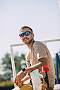 Smiling young man with earbuds and longboard in skatepark - VPIF00215