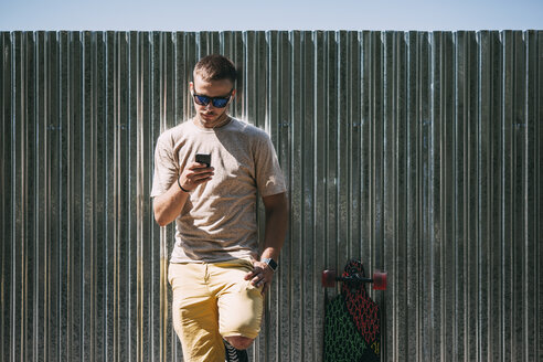 Young man with cell phone and earbuds leaning against a wall next to longboard - VPIF00221
