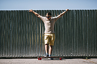 Young man with longboard standing at a wall - VPIF00227