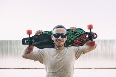 Portrait of confident young man with earbuds carrying longboard - VPIF00230