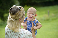 Mother playing with her baby girl in a park - LBF01658