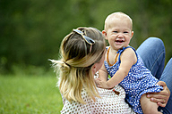 Mother playing with her baby girl in a park - LBF01661