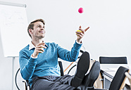 Smiling businessman juggling with balls in office - UUF11842