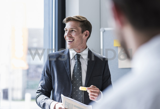 Smiling businessman in a meeting in office - UUF11854