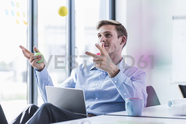 Businessman juggling with balls in office - UUF11860