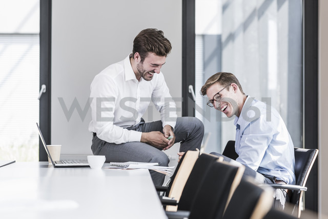 Two laughing colleagues in office - UUF11866