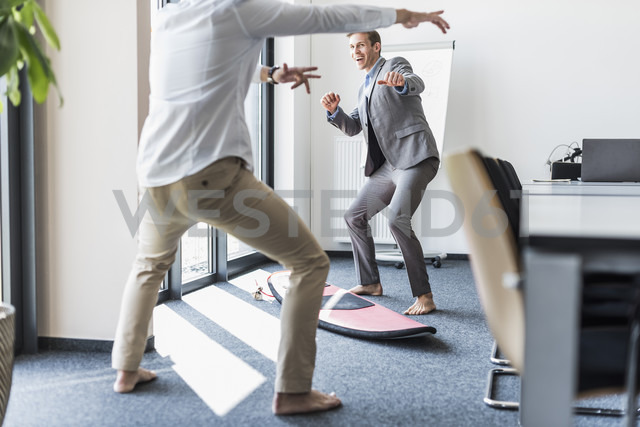 Two playful colleagues with surfboard in office - UUF11875