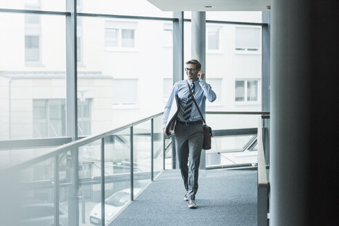 Happy businessman carrying surfboard in office - UUF11881