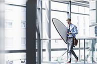 Businessman with cell phone carrying surfboard in office - UUF11884