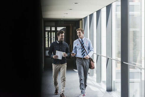 Two colleagues walking and talking on office floor - UUF11887