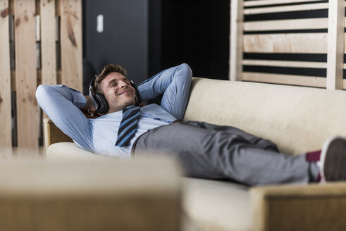 Businessman with headphones lying on couch in office lounge - UUF11899