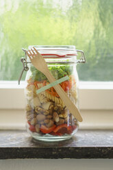 Preserving jar of vegan mixed salad with tofu and pasta on window sill - ECF01893