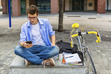 Young man with racing cycle sitting on bench looking at cell phone - MGIF00144