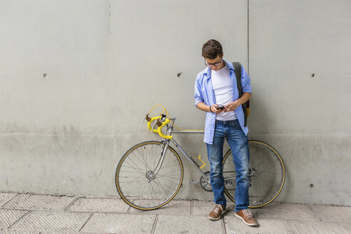 Young man with racing cycle looking at cell phone in front of concrete wall - MGIF00150