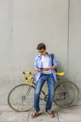 Young man with racing cycle looking at cell phone in front of concrete wall - MGIF00153