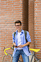 Portrait of smiling young man with racing cycle and cell phone standing in front of brick wall - MGIF00156
