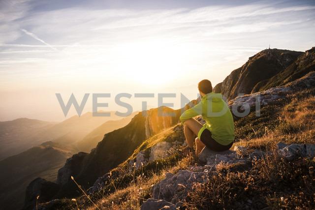 Italy, mountain running man sitting on rock looking at sunset - SIPF01790 - Simona Pilolla/Westend61