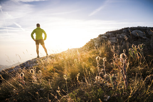 Italy, mountain running man standing on trail looking at sunset - SIPF01793