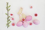 Hand dyed pink Easter eggs with bunny, daisy and catkin decoration on wooden background - GWF05262