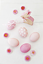 Hand dyed pink Easter eggs with bunny and daisy decoration on wooden background - GWF05265