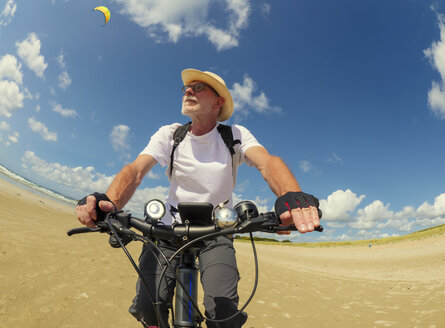 France, Bretagne, Sainte-Anne la Palud, Plage de Treguer, senior man riding mountain e-bike on beach - LAF01913