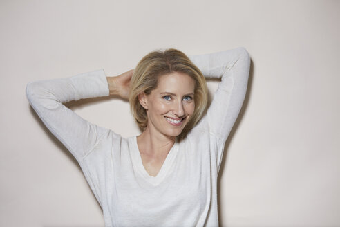 Portrait of smiling blond woman in front of light background - PNEF00007