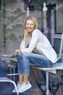 Portrait of laughing blond woman sitting on desk in an office looking out of the window - PNEF00010
