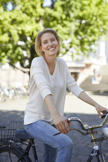 Portrait of laughing blond woman with bicycle - PNEF00016