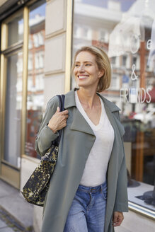 Portrait of smiling woman walking on pavement in front of a shop - PNEF00022