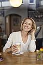 Portrait of happy woman with Latte Macchiato in a coffee shop - PNEF00025