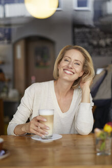 Portrait of happy woman with Latte Macchiato in a coffee shop - PNEF00025