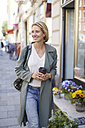 Portrait of smiling woman walking on pavement in front of a flower shop - PNEF00028