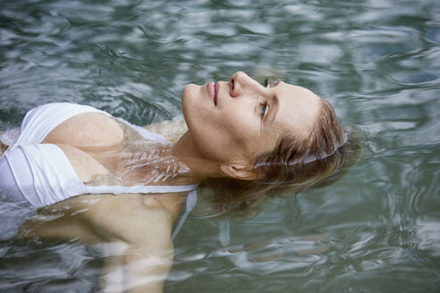 Portrait of relaxed woman floating on water - PNEF00049