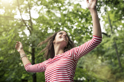 Happy young woman with raised arms dancing in nature - PNEF00051