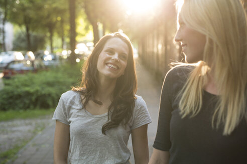 Two happy young women outdoors at sunset - PNEF00054