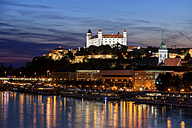 Slovakia, Bratislava, city at dusk with lighted Bratislava Castle and St. Martin's Cathedral at Danube River - ABOF00292