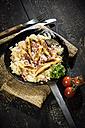 Frying pan of finger-shaped potato dumplings with sauerkraut and bacon on jute - MAEF12451