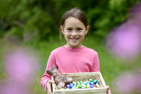 Portrait of happy little girl holding Easter nest - LBF01665