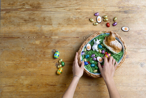 Hands filling Easter nest - LBF01668
