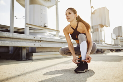 Young woman tying her shoes before workout - BSZF00050