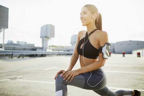 Smiling young woman wearing earphones stretching before jogging - BSZF00053