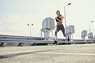 Young woman running in the city - BSZF00056