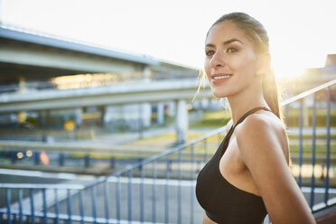 Portrait of smiling young woman during workout in the city - BSZF00059