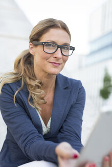 Portrait of confident businesswoman wearing glasses holding tablet in the city - PNEF00094